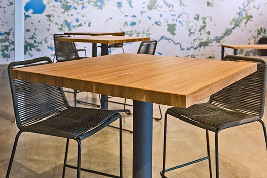 Single 30x30 restaurant table made of solid oak surrounded by brown chairs.