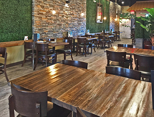 Rustic texture reclaimed Oak restaurant dining tables with green plants throughout and walls made of grass.