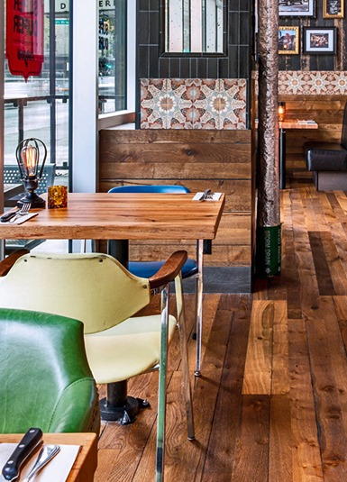 30x48 booth tabletop with leather seating, reclaimed barn wood wall coverings, flooring and local artwork.